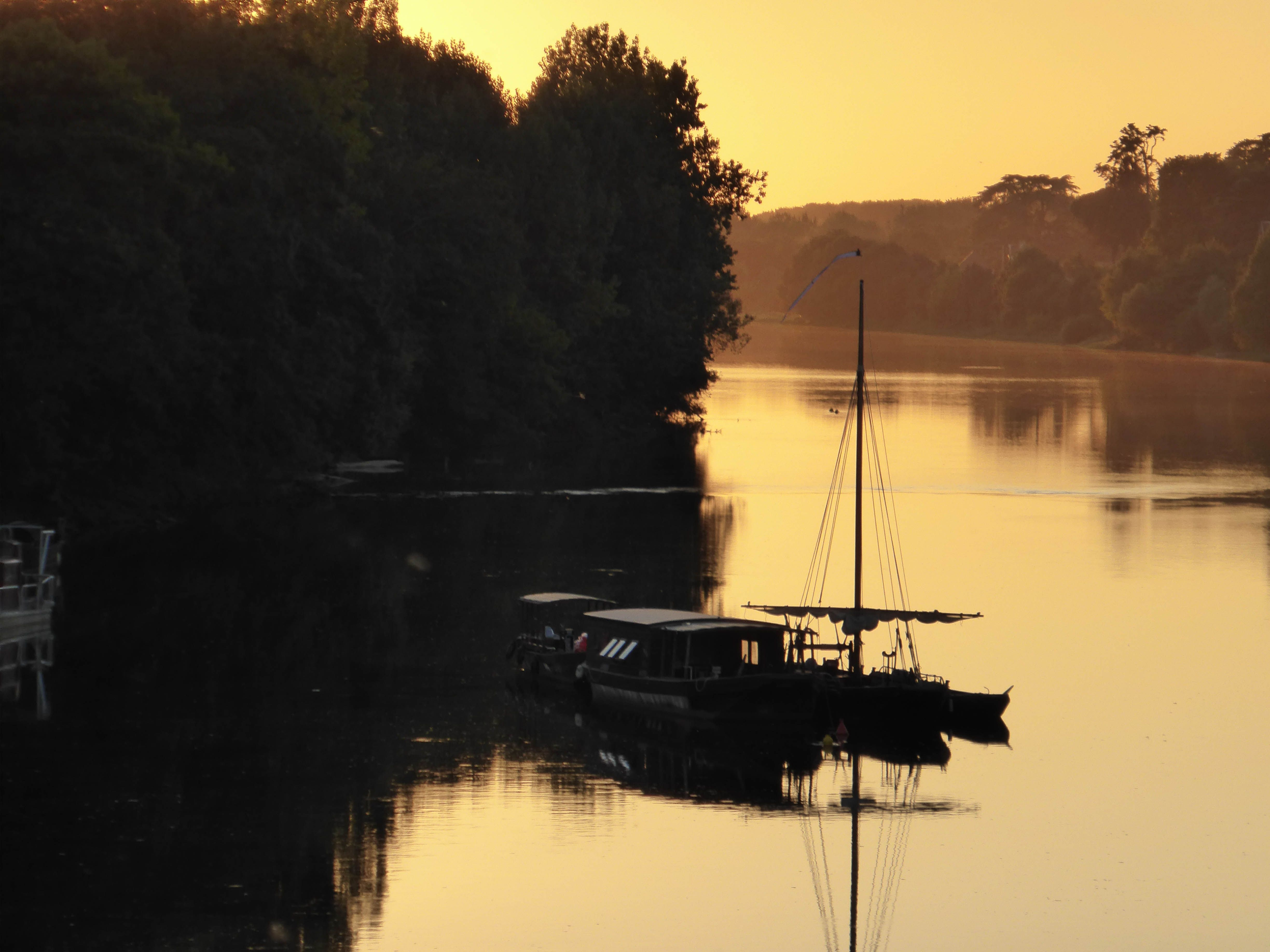 A very atmospheric view of the Vienne River near Chinon in France showing a Gabare or Flat Bottomed Boat at Sunset